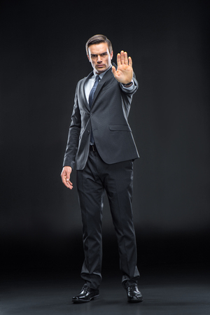 Handsome businessman in suit gesturing with palm and looking at camera