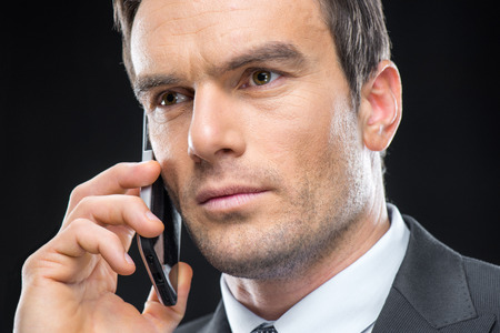 Close-up portrait of handsome businessman talking on smartphone