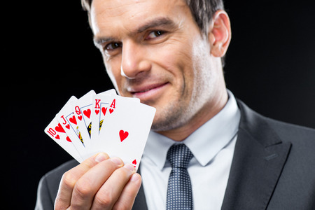 Smiling man showing playing cards with royal straight flush