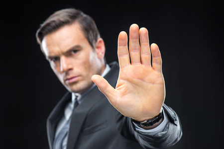 Close-up view of handsome businessman gesturing with palm and looking at camera