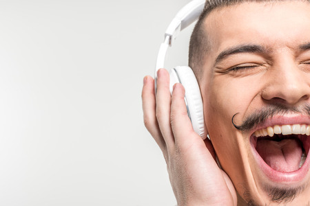 Happy young man in headphones singing on white