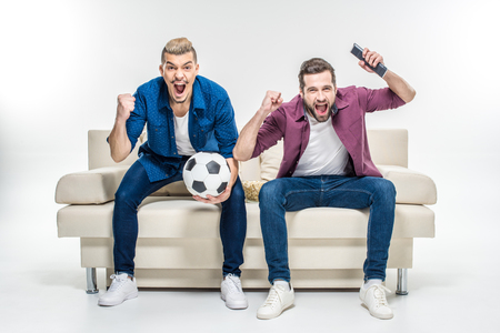 Emotional male friends sitting on couch with soccer ball and supporting favorite team