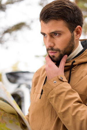 Close-up portrait of young bearded man holding map and standing near white car in autumn forest