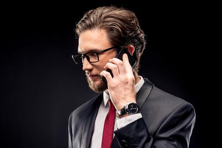 Handsome businessman in eyeglasses and suit talking on smartphone on black