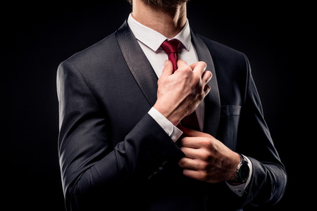 Mid section of businessman in black suit adjusting tie