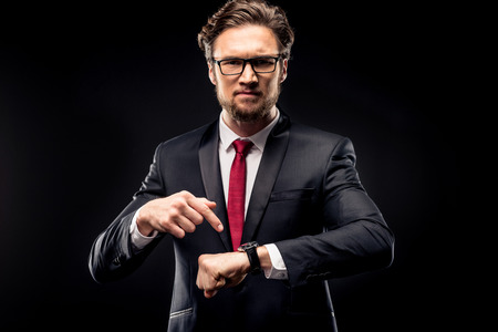 Annoyed businessman in black suit and eyeglasses pointing at wristwatch