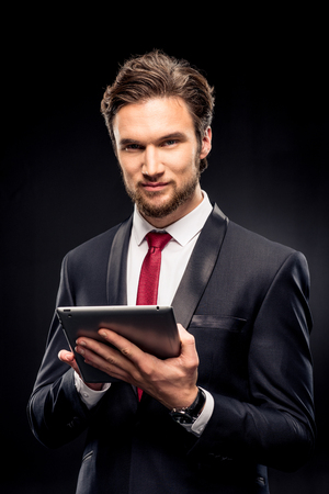 Handsome businessman in suit using digital tablet and looking at camera