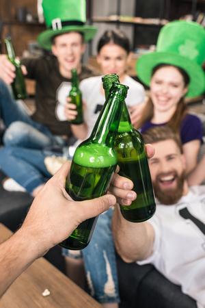 Photo pour friends clinking beer bottles - image libre de droit