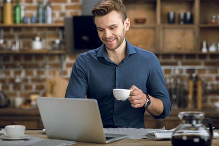 Photo for young man using laptop while drinking coffee at home - Royalty Free Image