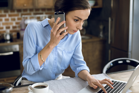 Photo for young woman talking on smartphone while using laptop - Royalty Free Image