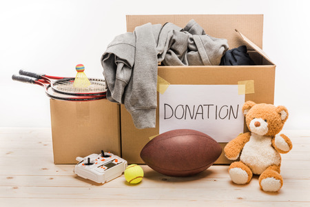 cardboard boxes with donation clothes and different objects on white, donation concept