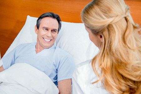 middle aged patient lying on bed and doctor sitting near him
