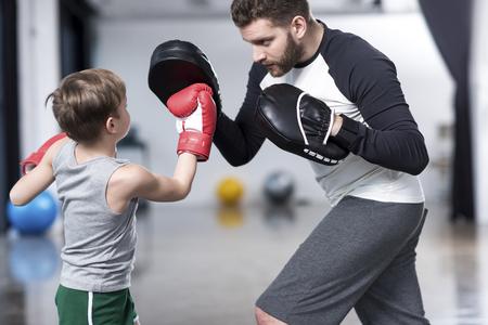 Photo pour boy boxer practicing punches with coach - image libre de droit