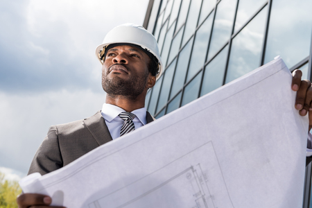 Photo for professional architect in hard hat holding blueprint outside modern building - Royalty Free Image