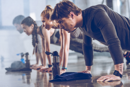group of athletic young people in sportswear doing push ups or plank at the gym