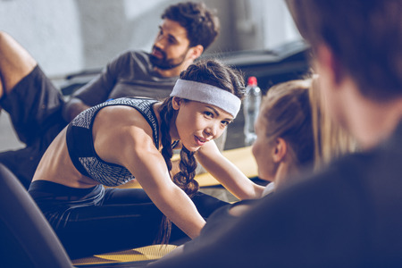 young people lying on yoga mats and exercising at the gym