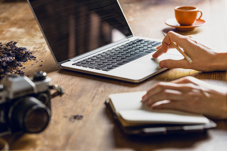 Photo for person using laptop and diary at workspace with vintage camera - Royalty Free Image