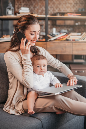 Photo for Mother smiling and working at home while taking care of her son - Royalty Free Image