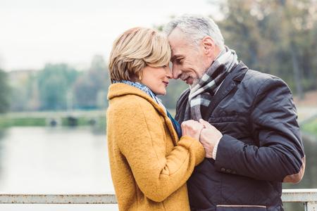 Photo pour Beautiful mature couple standing near lake - image libre de droit