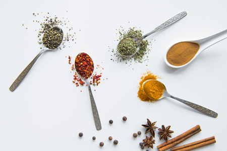 various dried aromatic spices in metal and ceramic spoons