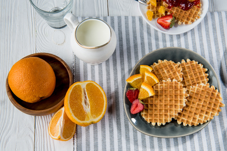 fresh tasty breakfast with waffles and milk on table top