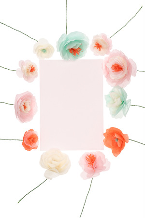 Beautiful handmade flowers arranged around blank greeting card