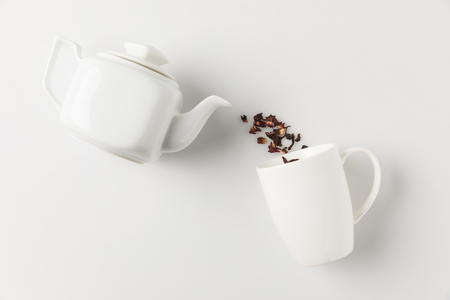 composition of tea pouring from pot into cup on white surface
