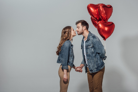 Photo pour side view of young couple able to kiss while man holding red heart shaped balloons - image libre de droit
