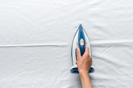 man ironing bed sheets