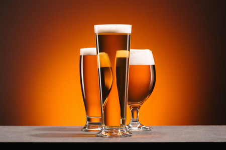 Foto de close up view of arrangement of glasses of beer on orange backdrop - Imagen libre de derechos