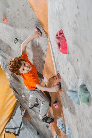 High-angle shot of little red-headed boy climbing a wall with grips and looking at camera