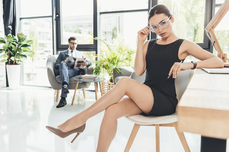 Foto de Young businesswoman in black dress and glasses sitting in a chair at office with legs crossed - Imagen libre de derechos
