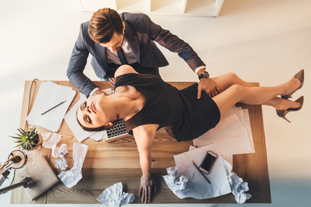 Young woman in little black dress sitting on a desk in office with man in business suit standing over her and touching her thigh