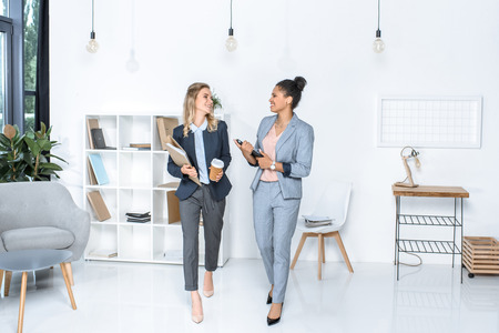 Photo pour multicultural businesswomen having conversation while walking in office - image libre de droit