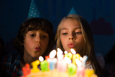 cute little children on party hats blowing candles on birthday cake