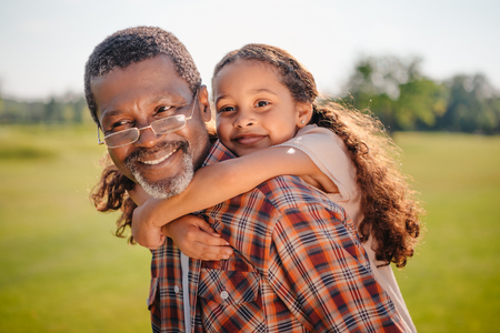 Photo pour happy african american granddaughter hugging her smiling grandfather on green lawn  - image libre de droit