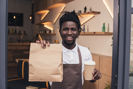 smiling african american barista holding disposable cup of coffee and kraft package