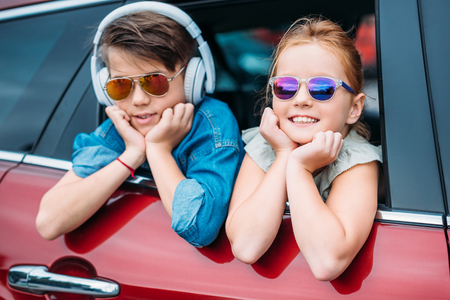 Foto de happy kids in sunglasses on car trip looking out of window - Imagen libre de derechos