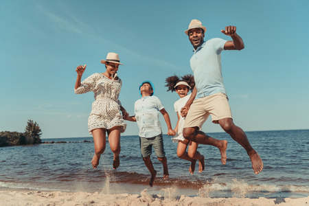 Photo pour happy african american family holding hands and jumping on beach - image libre de droit