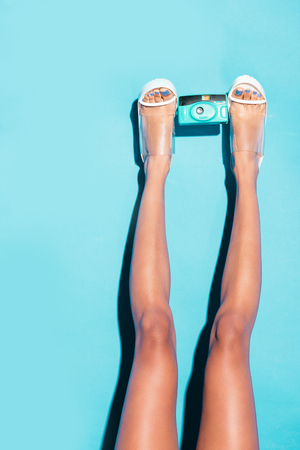 cropped view of female legs in heels holding retro photo camera,  on turquoise