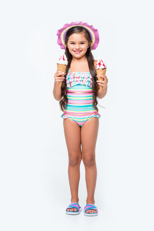 Foto de cute little girl in swimsuit holding ice cream and smiling at camera  - Imagen libre de derechos