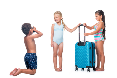 Foto de african american boy kneeling and photographing happy little girls with suitcase isolated on white - Imagen libre de derechos