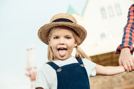 Photo pour portrait of little girl sticking tongue out and looking at camera - image libre de droit