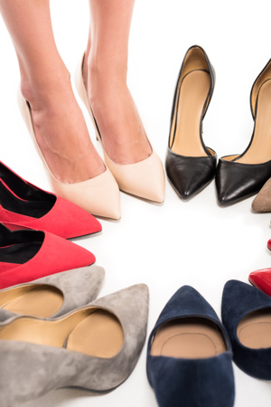 partial view of woman standing in circle with arranged stylish high heels isolated on white