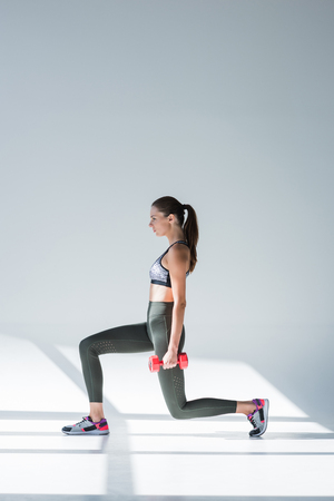 Foto de side view of sporty young woman exercising with dumbbell on grey - Imagen libre de derechos