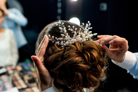 Photo for partial view of hairstylist decorating clients hairstyle with beautiful accessory - Royalty Free Image