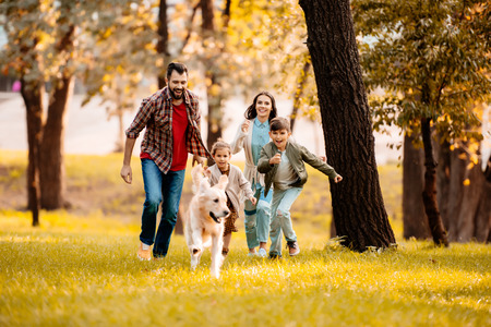 Foto de Happy family with two children running after a dog together in autumn park - Imagen libre de derechos