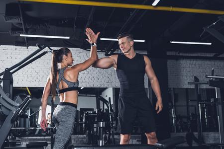 Foto de sportive couple giving high five to each other in gym - Imagen libre de derechos