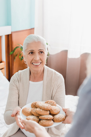 cropped shot of nurse giving plate with cookies to smiling senior woman sitting on bed