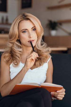 Foto de pensive blonde woman writing in notebook and looking away - Imagen libre de derechos